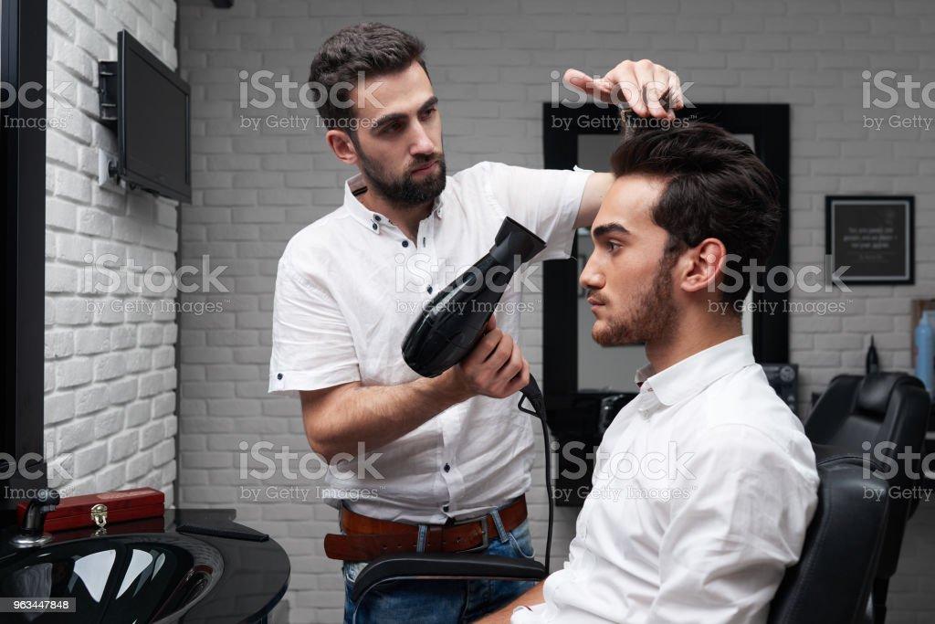 coiffeur professionnel est sécher les cheveux du client avec sèche-cheveux - Photo de Adulte libre de droits