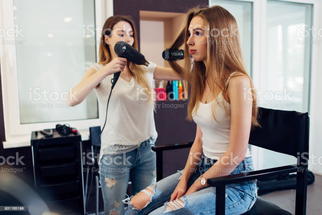 professional hairstylist using hairdryer and round brush to style long fair hair of the female customer