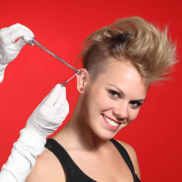 professionelle hände ball-piercing loch auf mode frau - ohrringe piercing stock-fotos und bilder
