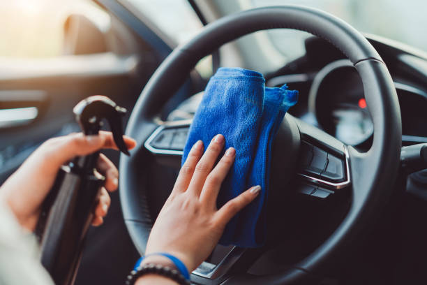 professional hands of woman cleaning steering wheel and console car using microfiber cloth protection in interior for shiny after wash a car and vacuum cleaner. - gmail imagens e fotografias de stock