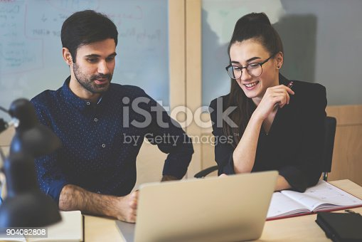 905130626 istock photo Professional handsome business coach training young female students presenting application for financial accountings on laptop computer, journalist watching streaming video for creating article 904082808