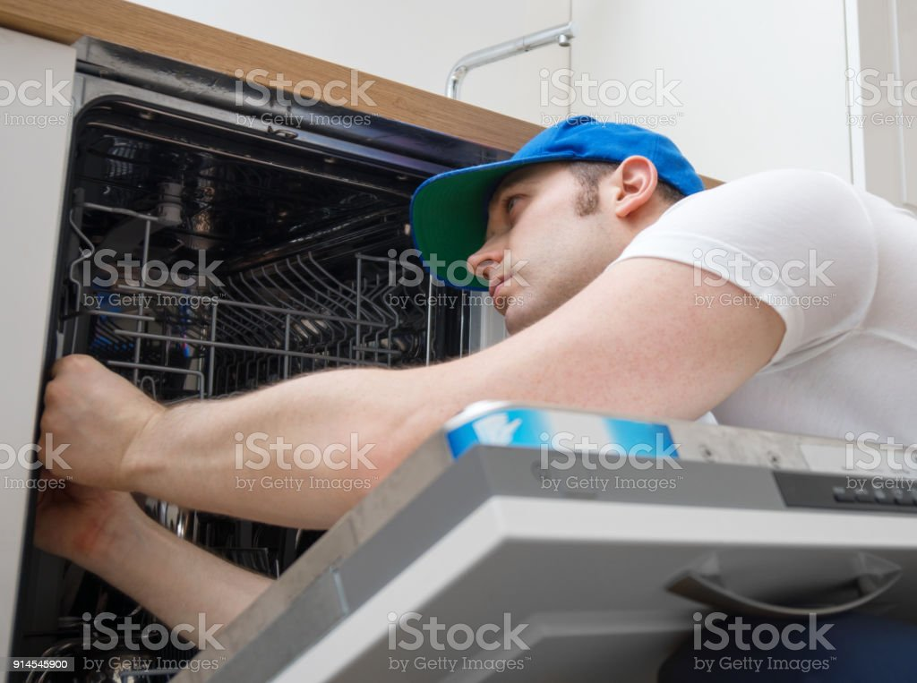Professional handyman in overalls repairing domestic dishwasher in the kitchen. stock photo