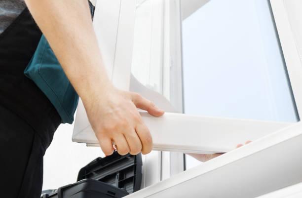 Professional handyman installing window at home. stock photo
