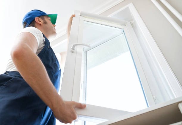 Professional handyman installing window at home. stock photo