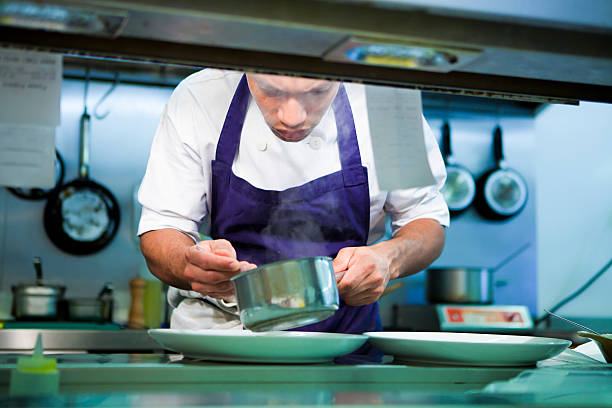 Professional head chef who is plating up for dinner service stock photo