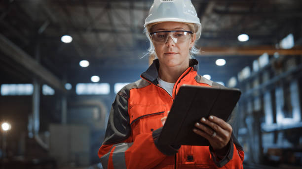 Professional Heavy Industry Engineer/Worker Wearing Safety Uniform and Hard Hat Uses Tablet Computer. Serious Successful Female Industrial Specialist Walking in a Metal Manufacture Warehouse. stock photo