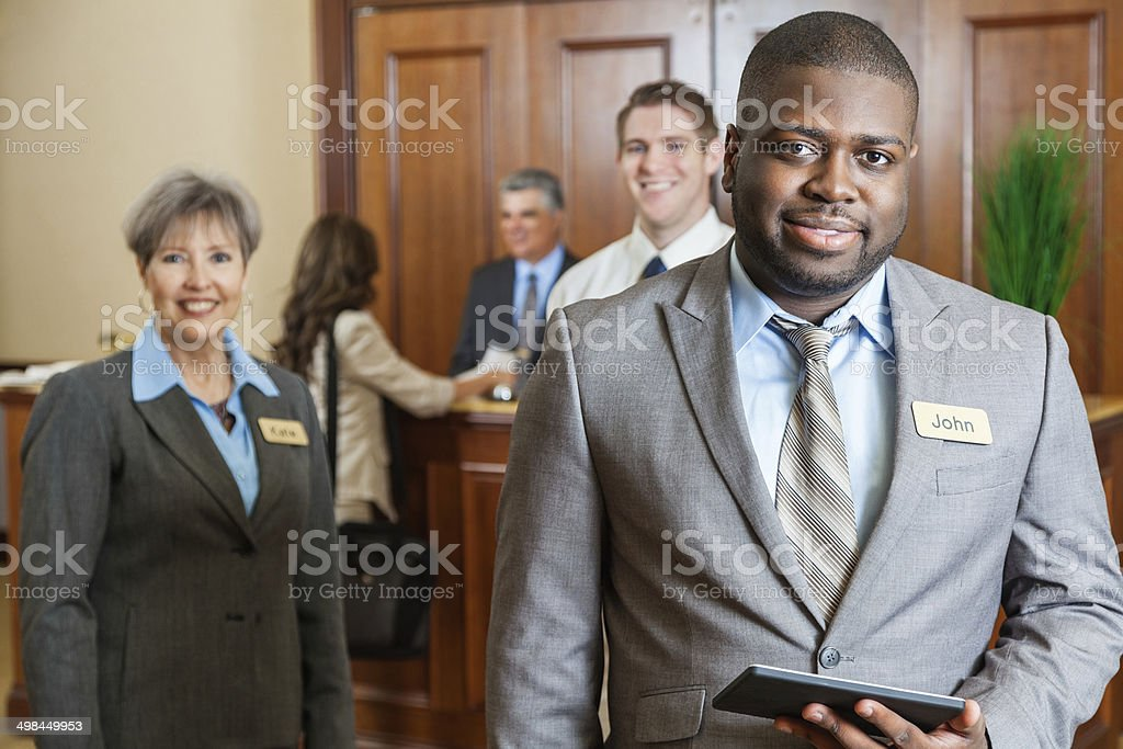 Professional hotel manager standing with staff in lobby stock photo