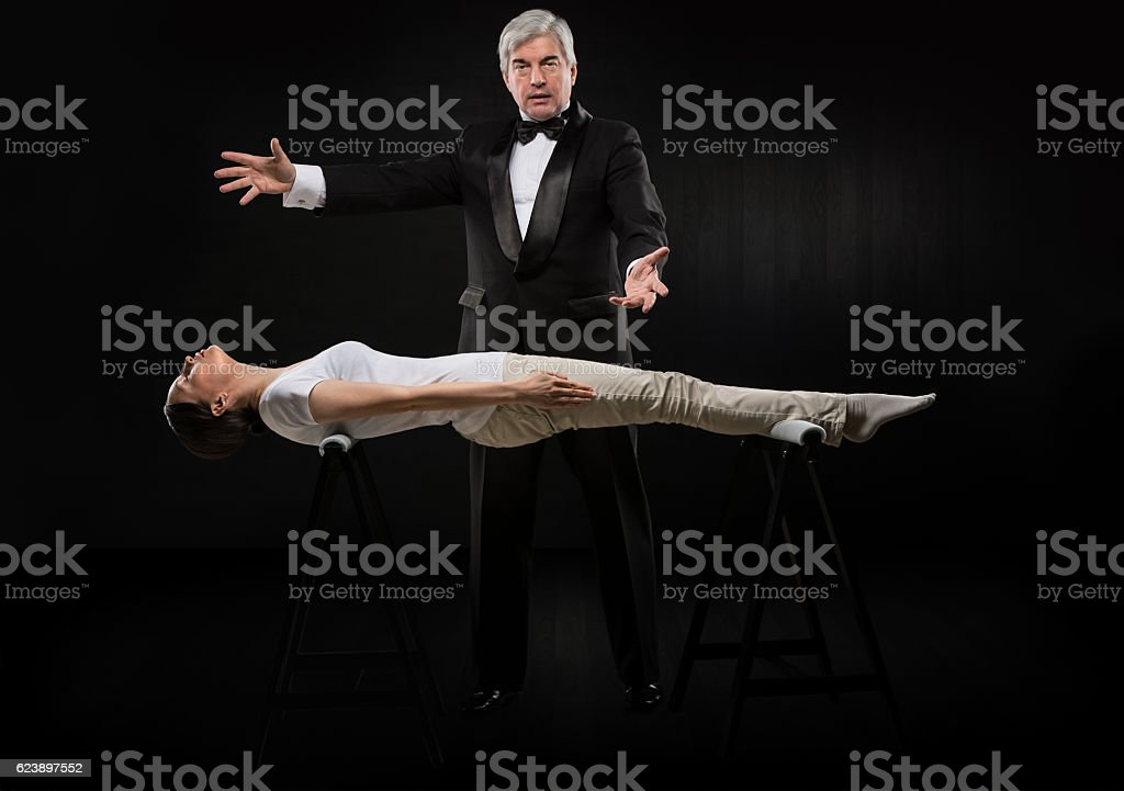 Professional hypnotist on black background working with woman stock photo