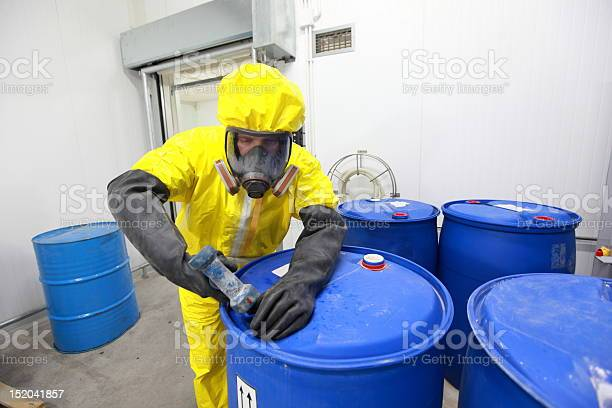 Fully protected in yellow uniform,mask,and gloves professional filling barrel with chemicals