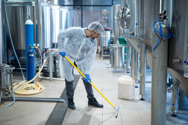 limpador industrial profissional no assoalho de limpeza uniforme protetor da planta de processamento de alimento. serviços de limpeza. - higiene - fotografias e filmes do acervo
