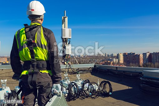 Professional industrial climber in helmet and uniform with telecomunication equipment in his hand and  antennas of GSM  DCS UMTS LTE bands, outdoor radio units  on the roof. Working process of upgrading telecommunication equipment