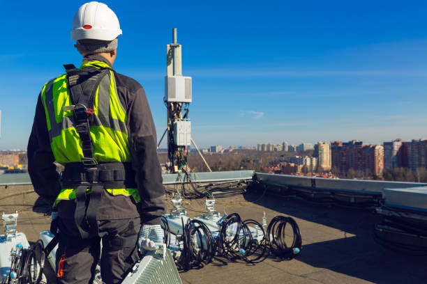 Professional industrial climber in helmet and uniform with telecomunication equipment in his hand and  antennas of GSM  DCS UMTS LTE bands, outdoor radio units  on the roof. Working process of upgrading telecommunication equipment. Professional industrial climber in helmet and uniform with telecomunication equipment in his hand and  antennas of GSM  DCS UMTS LTE bands, outdoor radio units  on the roof. Working process of upgrading telecommunication equipment telecommunications equipment stock pictures, royalty-free photos & images