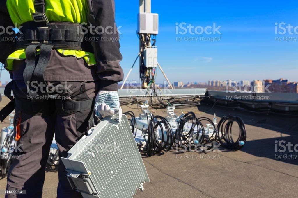 Escalador industrial profesional en casco y uniforme con equipo de telecomunicación en su mano y antenas de bandas GSM DCS UMTS LTE, unidades de radio al aire libre en el tejado. Proceso de mejora de equipos de telecomunicación. - Foto de stock de Accesorio de cabeza libre de derechos