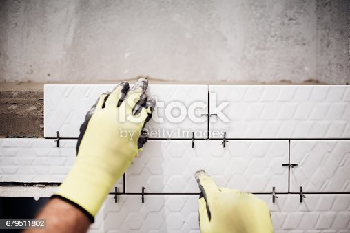istock Professional industrial worker installing small ceramic tiles in bathroom during renovation works 679511802