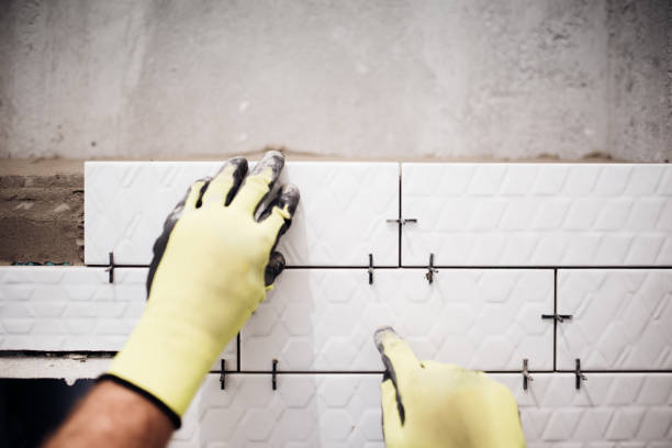 professional industrial worker installing small ceramic tiles in bathroom during renovation works - betonkleber stock-fotos und bilder