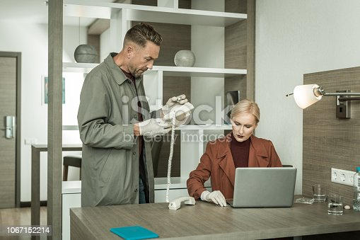 istock Professional inspector in raincoat setting some spy device 1067152214