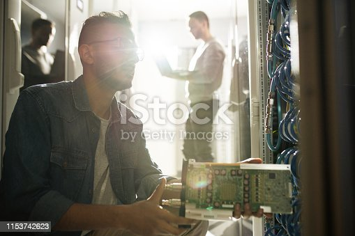 istock IT professional installing blade server 1153742623