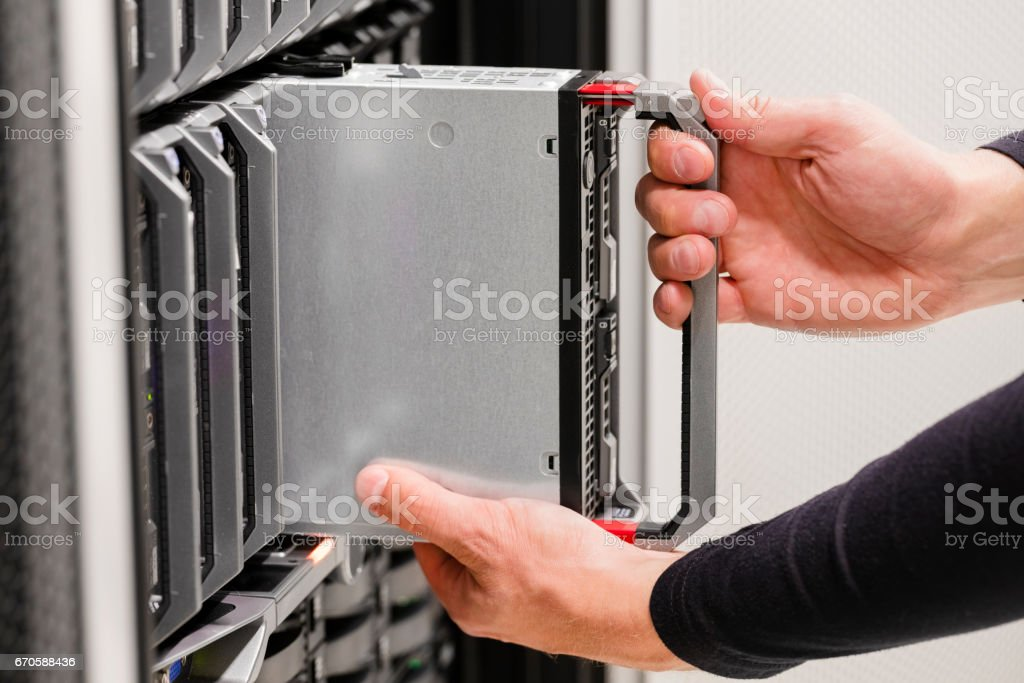 IT professional installs server cluster in large datacenter stock photo