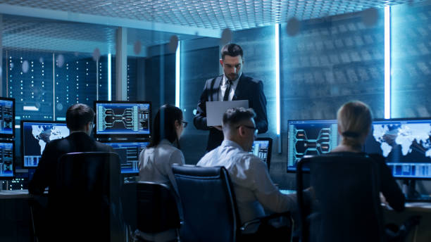 professional it engineers working in system control center full of monitors and servers. supervisor holds laptop and holds a briefing. possibly government agency conducts investigation. - spy stock photos and pictures