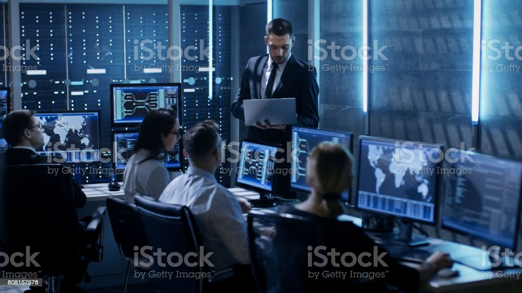 Professional IT Engineers Working in System Control Center Full of Monitors and Servers. Supervisor Holds Laptop and Holds a Briefing. Possibly Government Agency Conducts Investigation. stock photo