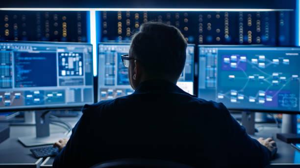 Professioneller IT-Programmierer arbeitet im Rechenzentrum auf Desktop-Computern mit drei Displays, Entwicklung von Software und Hardware. Displays zeigen Blockchain, Data Network Architecture Concept – Foto