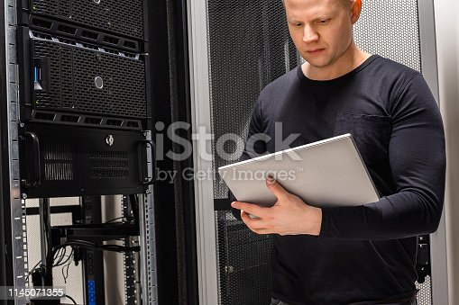 istock Professional IT Support Using Digital Tablet By Servers In Datacenter 1145071355