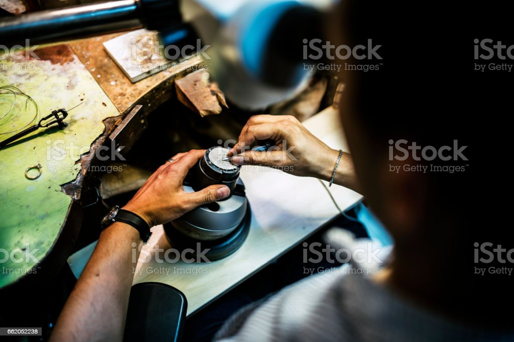 Professional jeweler working on a pieces of metal using an optical device royalty-free stock photo
