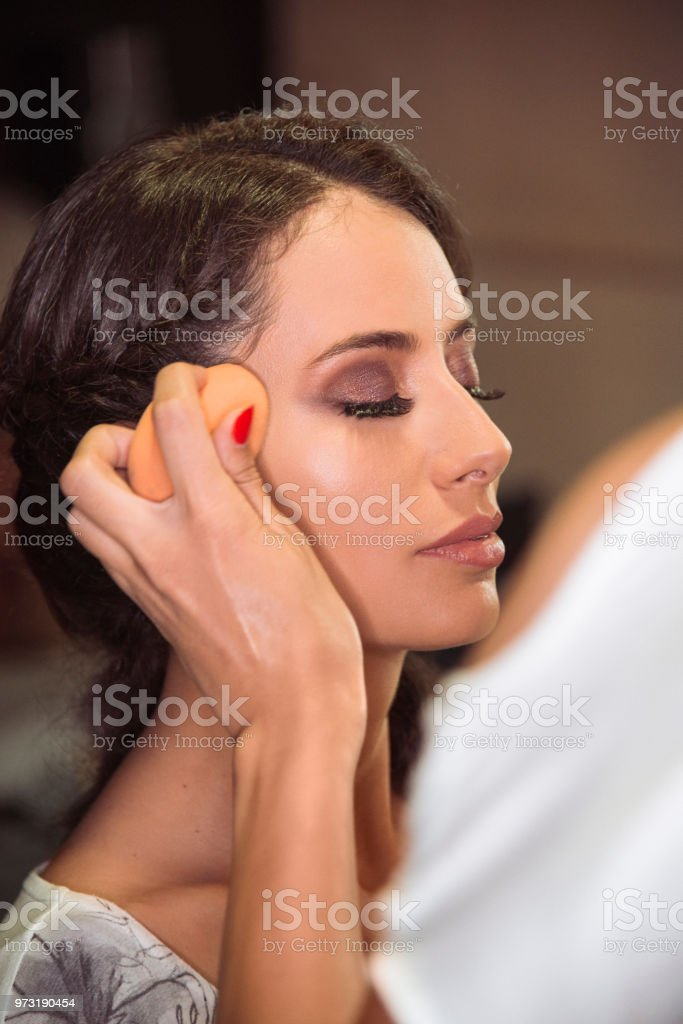 Professional make up artist working on a beautiful model in the studio stock photo