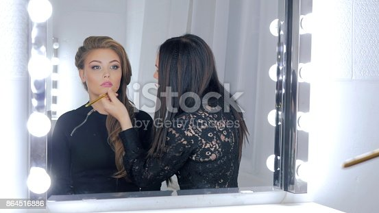 istock Professional make-up artist applying lip gloss 864516886