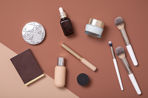 Professional make-up artist flat lay on beige background for fashion woman.