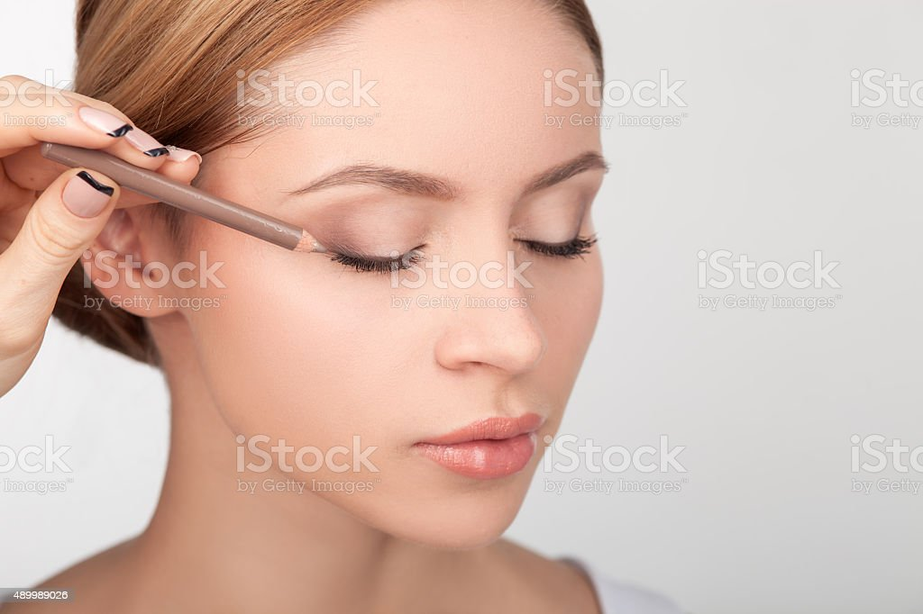Professional makeup artist is painting female eyes stock photo