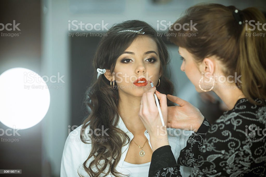 Professional makeup artist makes up lips beautiful, attractive model, celebrity. stock photo