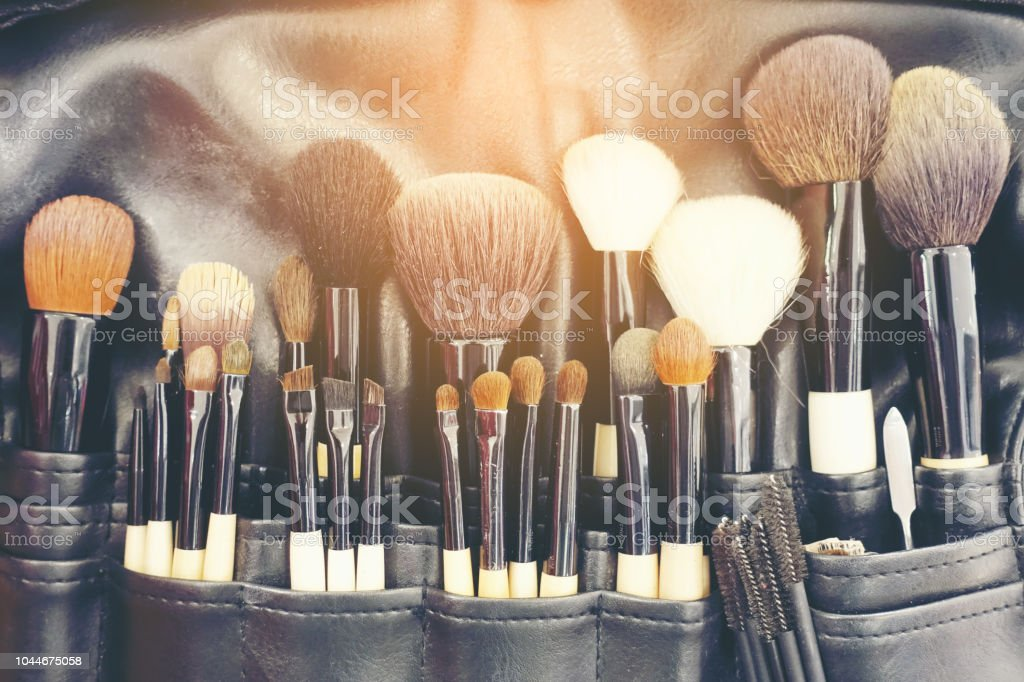 Professional makeup brushes cosmetic in tube, leather bag. close-up brush, makeup tools of , powder, set of different objects for makeup artist in their holder. Set of make up products arranged stock photo
