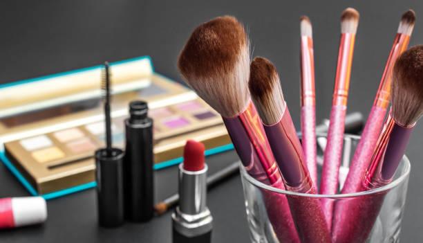 professionelle make-up bürsten mit anderen kosmetik-tools auf schwarzem schreibtisch. - natürliche make up kurse stock-fotos und bilder