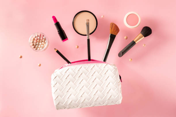 Professional makeup, flying out of a bag, on a pink background. Lipstick, brushes, powder compact, a creative beauty design stock photo
