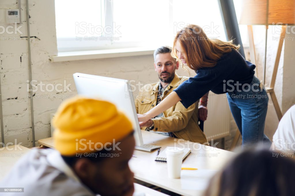 Professional male and female colleagues talking to each other pointing on advantages of new application installed on modern computer, mature coach feeling confused with bad internet connection stock photo