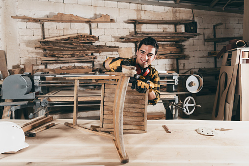 530997702 istock photo Professional male carpenter repairing antique furniture in workshop, varnishing vintage chair 1266561248