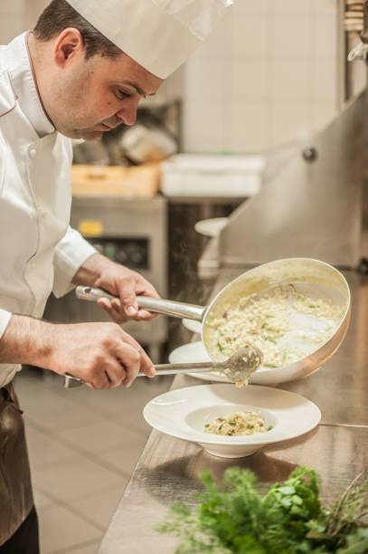 Professioneller männlicher Küchenchef bereitet traditionelles italienisches Risotto mit Spargel vor – Foto