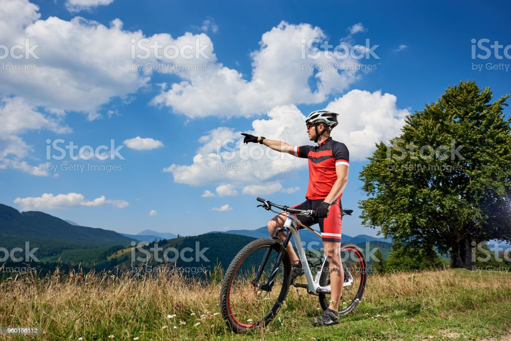 Professional male cyclist standing with bike on grassy valley, resting after cycling stock photo