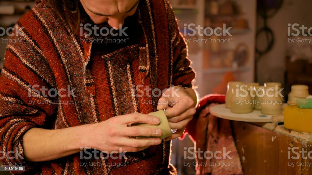 Professional male potter making mug in pottery workshop stock photo