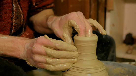 Professional male potter working in workshop