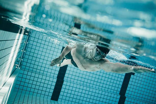 professional male swimmer inside swimming pool - vuelta completa fotografías e imágenes de stock