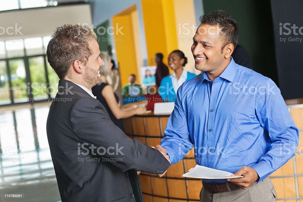 Professional man meeting employee with resume at job fair event stock photo