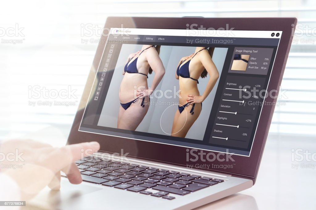 Professional man using laptop to transform chubby woman slim. Heavy photo editing with computer software. Standard of beauty, body image and post production concept. stock photo