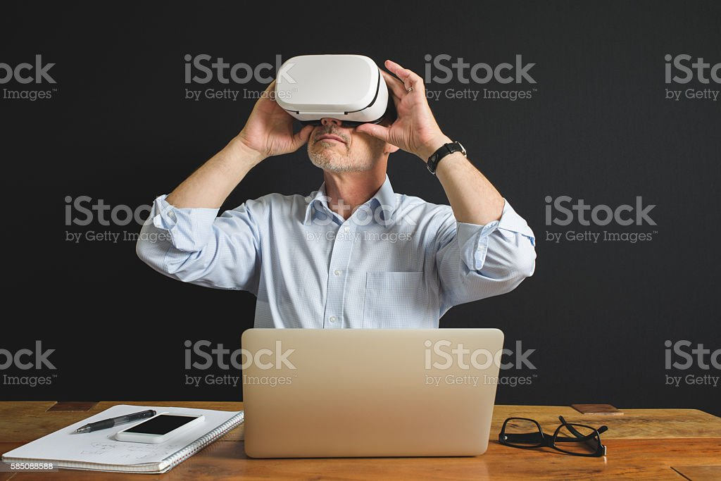 Professional Man Using Virtual Reality Headset Laptop and Smartphone stock photo