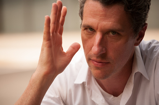 Professional man with raised hand in forceful gesture