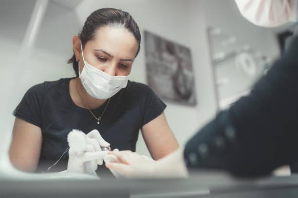 Maestro profesional de manicura vestido negro con máscara facial de seguridad usando herramienta de pulidor de uñas eléctrica para el procedimiento de manicura de tratamiento de acristalamiento. Concepto de trabajo diario de pequeñas empresas. - foto de stock