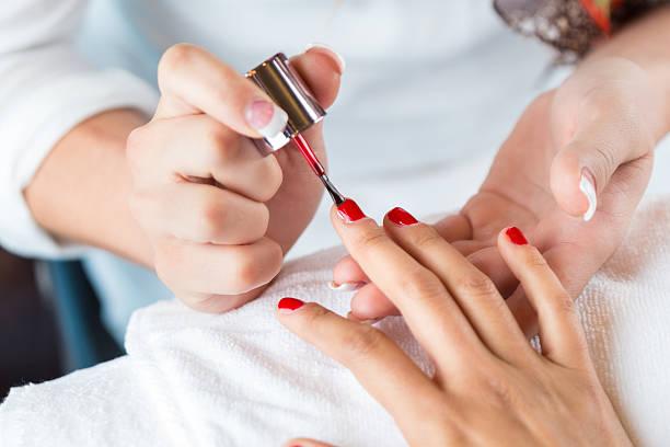 professionelle manikürist/in benutzt roten nagellack zum kunden hände - nägel lackieren stock-fotos und bilder