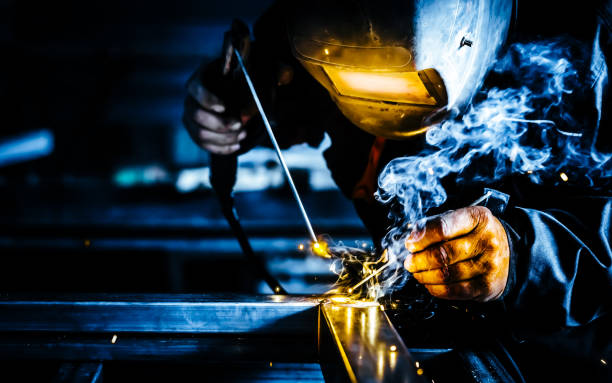 Professional mask protected welder man working on metal welding and sparks metal. Professional mask protected welder man working on metal welding and sparks metal. metalwork stock pictures, royalty-free photos & images