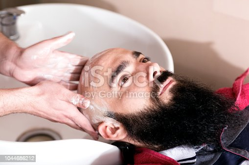 928445950 istock photo Professional master hairdresser preparing client's head shaving 1044686212